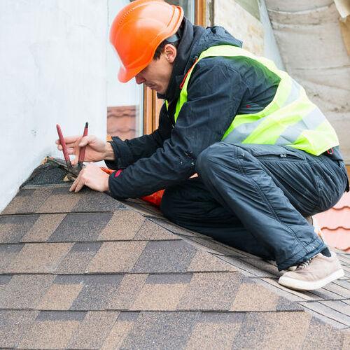 A Roofer Removes Damaged Shingles.